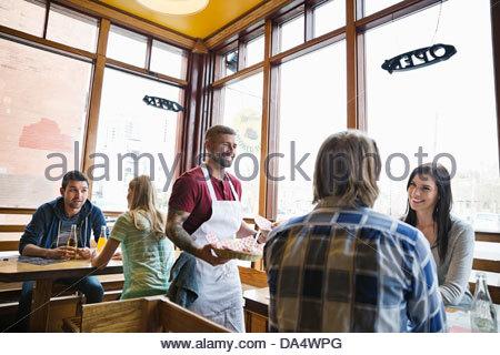 Maschio proprietario Deli che serve cibo ai clienti Foto Stock