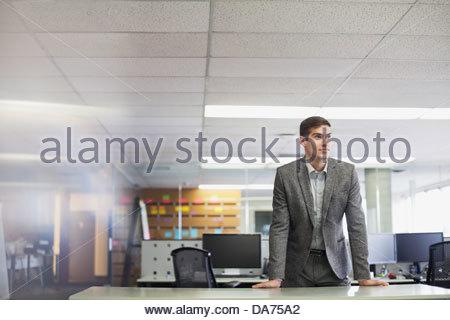 Imprenditore appoggiato sulla scrivania in ufficio Foto Stock