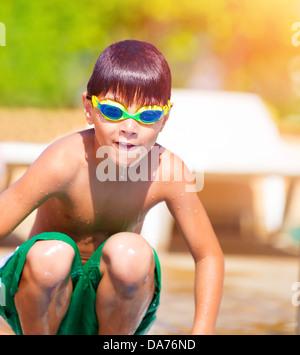 Ragazzo sportivo il salto in piscina, indossando occhiali nuotatore, attiva l'infanzia, sport d'acqua, vacanze estive Foto Stock