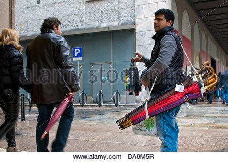 Immigrati bengalesi che vende ombrelloni,Milano,Italia Foto Stock