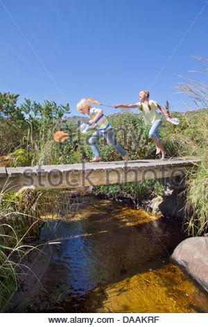 Ragazza ragazzo insegue con rete da pesca sulla passerella sul torrente Foto Stock