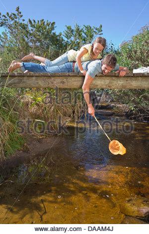 Padre e figlia posa sulla passerella e immersione rete da pesca nel flusso Foto Stock