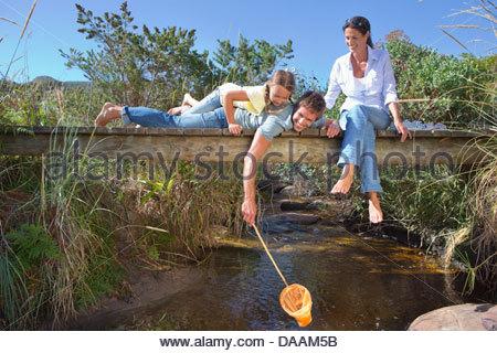 Famiglia posa sulla passerella e immersione rete da pesca nel flusso Foto Stock