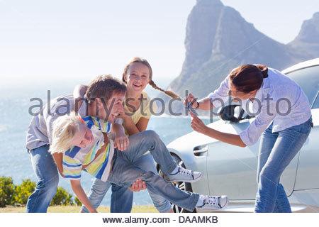 Madre di fotografare la famiglia felice giocando fuori auto nei pressi di ocean Foto Stock