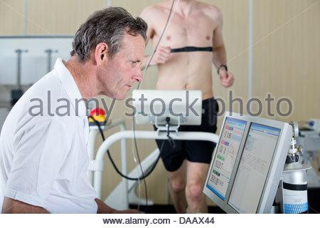 Sport Scientist presso il computer e guida sul tapis roulant in laboratorio Foto Stock