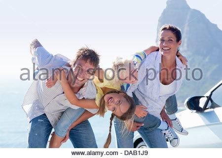 Ritratto di famiglia felice accanto a auto con l'oceano sullo sfondo Foto Stock