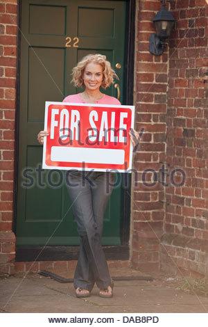 Una donna matura in possesso di una proprietà in vendita segno Foto Stock