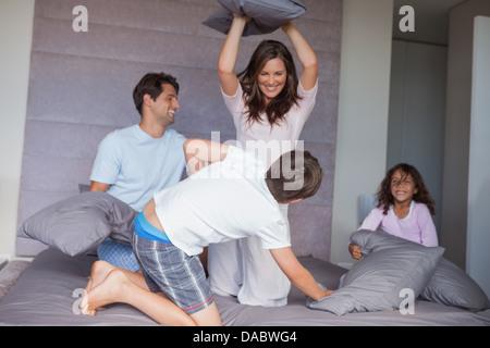 Famiglia avente una lotta di cuscini sul letto Foto Stock