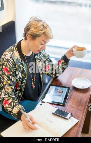 Donna fare chiamata video scrittura nel blocco note in cafe