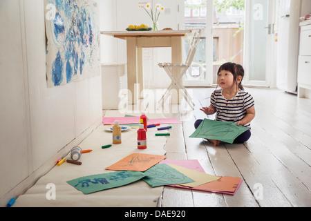 Femmina bambino seduto sul pavimento con disegni Foto Stock