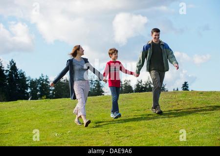Genitori e figlio camminando mano nella mano Foto Stock