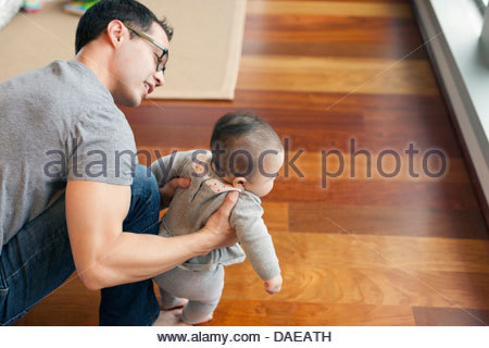 Padre il supporto di bambina a camminare Foto Stock