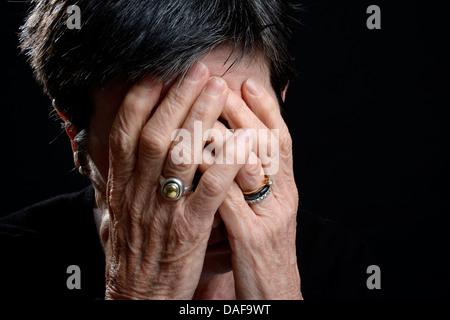 Triste vecchia donna che copre il volto con le mani / piangendo, salute mentale concetto Foto Stock