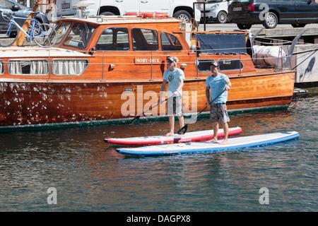 Due uomini stand up paddle imbarco sul canale di Nyhavn, Copenhagen, Danimarca Foto Stock