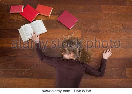 Giovane donna sdraiata sul pavimento con sovraccarico di studio Foto Stock
