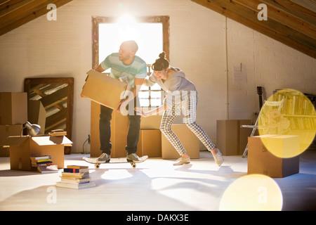 Giovane disimballaggio scatole in soffitta Foto Stock