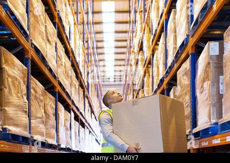 Lavoratore scatola portante in magazzino Foto Stock