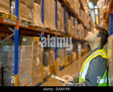 Lavoratore di caselle di controllo in magazzino Foto Stock