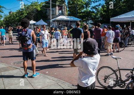 Le persone godono di musica all'aperto a Ballard Seafood Festival di Seattle Foto Stock