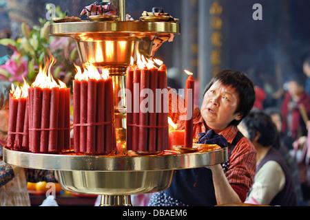 Una donna riaccende il fuoco al tempio Longshan in Taipei, Taiwan. Foto Stock
