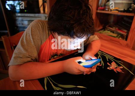 Un bambino di nove anni utilizzando un Apple IPod iPodTouch o IPhone iPhone o IPad lettore multimediale portatile Foto Stock