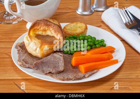 Roast Beef e Yorkshire pudding - con il sugo di carne, arrosto di patate, piselli e carote. Foto Stock