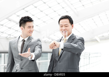 La gente di affari controllando il tempo in aeroporto lobby Foto Stock