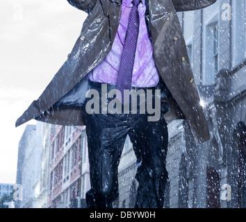 Imprenditore in esecuzione in caso di pioggia Foto Stock