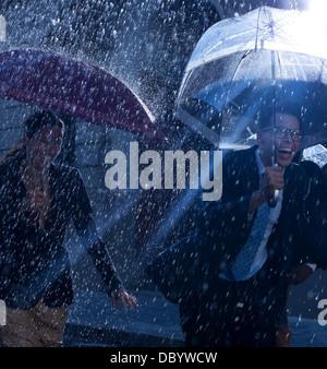 Felice la gente di affari in esecuzione con gli ombrelli in caso di pioggia Foto Stock