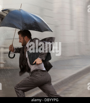 Imprenditore con ombrellone in esecuzione in caso di pioggia Foto Stock