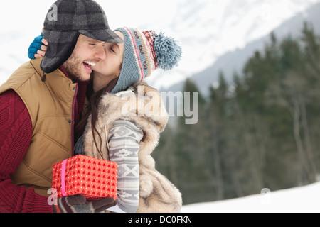 Coppia felice con un regalo di Natale baciare in campo nevoso Foto Stock