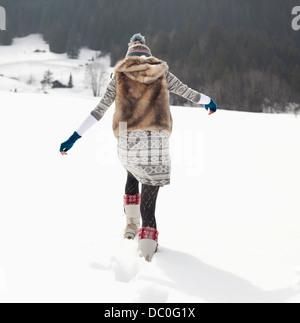 Donna che cammina nel campo nevoso Foto Stock