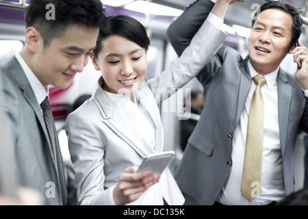 Allegro per persone d' affari con il cellulare in treno della metropolitana Foto Stock
