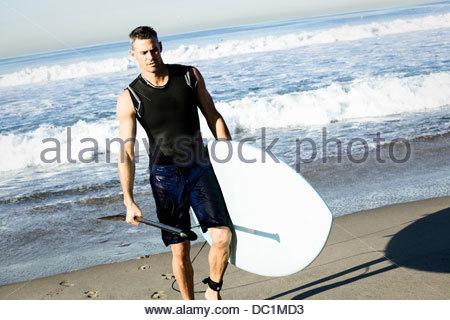Metà uomo adulto surfer camminando sulla spiaggia con la tavola da surf Foto Stock