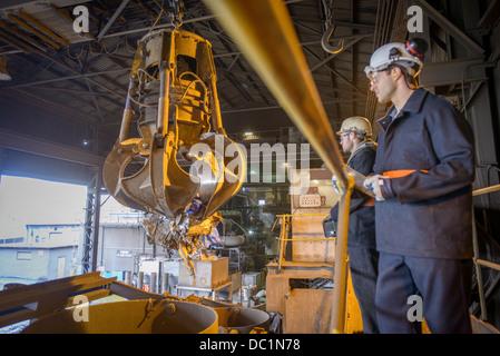 Lavoratori guardando meccanica grabber in fonderie di acciaio Foto Stock