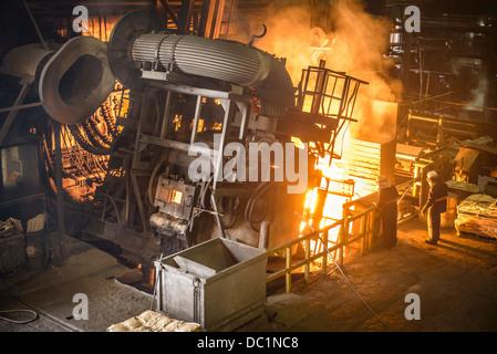 I lavoratori e i macchinari in fonderia di acciaio Foto Stock
