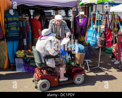 Coppia di anziani a fare shopping con la mobilità scooter a Sidmouth, nel Devon, Inghilterra Foto Stock