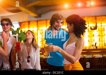Il gruppo di amici con i cocktail del bar Foto Stock