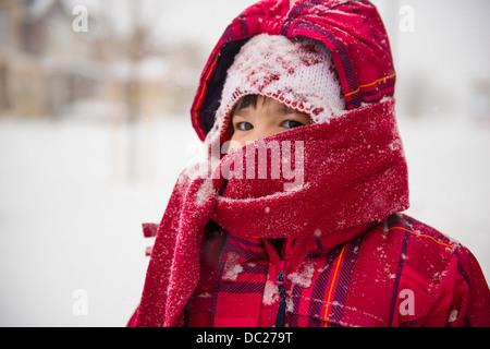 Ragazza indossando coat, sciarpa e cappello con il cofano Foto Stock