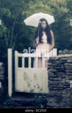 Una bella donna con lunghi capelli neri in piedi in un vintage abito rosa e un ombrellone dietro un cancello Foto Stock