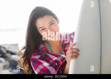 Giovane donna indossa controllato shirt con tavola da surf Foto Stock
