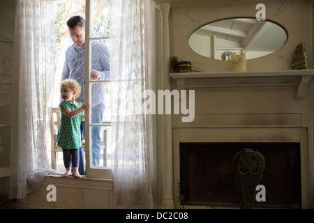 Padre e figlio entrando in camera dalla veranda Foto Stock