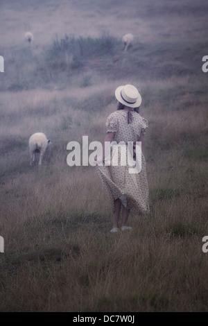 Una ragazza in un abito vintage su un prato con le pecore Foto Stock