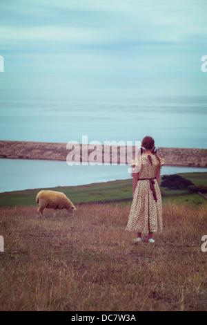 Una ragazza in un abito vintage su un prato con una pecora Foto Stock