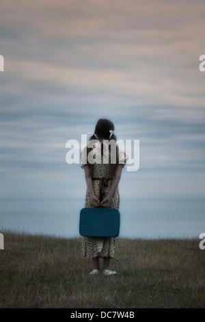 Una ragazza in un abito vintage con la valigia Foto Stock