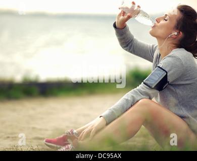 Runner donna seduta sul prato mentre acqua potabile Foto Stock
