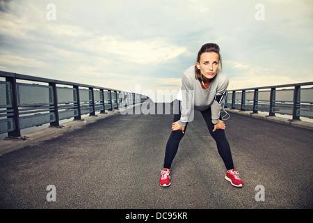 Runner focalizzato all'aperto in appoggio sul ponte Foto Stock
