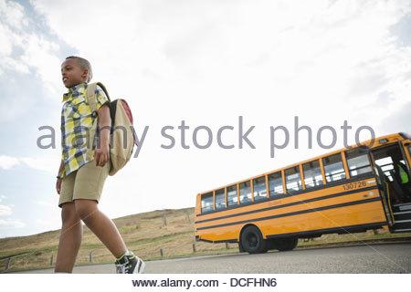 Basso angolo vista di scolaro a piedi dalla scuola bus Foto Stock