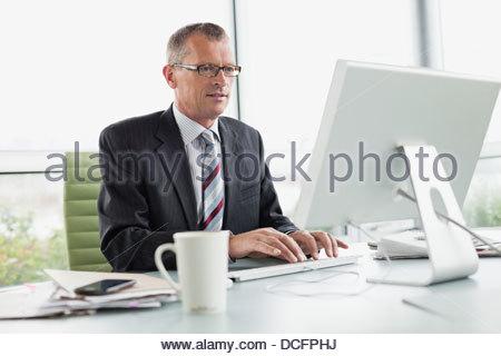 Imprenditore lavorando sul computer in ufficio Foto Stock