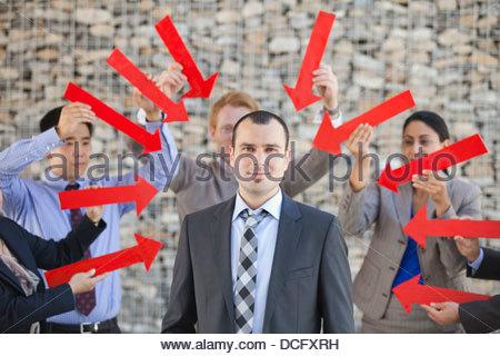 Un gruppo di uomini di affari che le frecce rivolte verso l'uomo d'affari Foto Stock